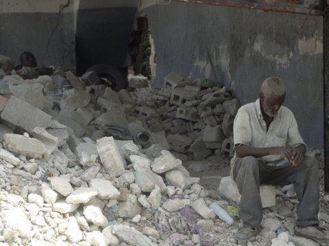 Zwei Männer sitzen auf den Trümmern eines durch das Erdbeben zerstörten Hauses.  August 2010, Port-au-Prince, Haiti