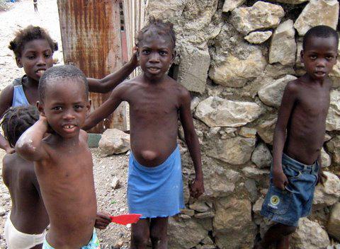 Kinder vor einer Mauer.  Juni 2010, La ville Dessalines Artibonite, Haiti