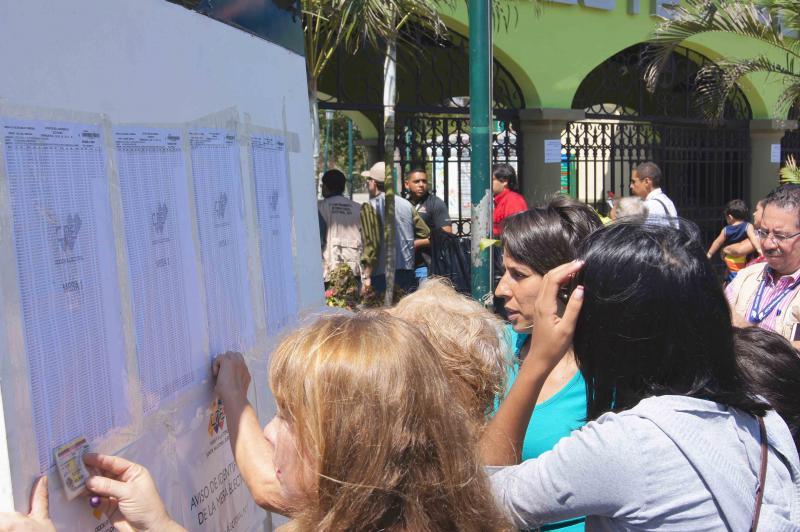 Vor den Wahlbüros informieren sich die Wählerinnen und Wähler anhand ihrer Ausweisnummer, an welchem Wahltisch sie ihre Stimme abgeben können.