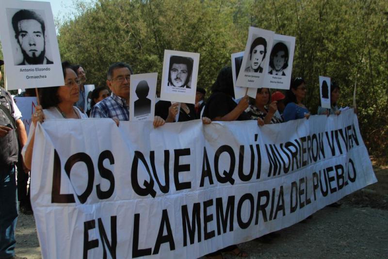 """Angehörige mit Bildern von Verschwundenen. Auf dem Transparent: """"Die hier starben, leben in der Erinnerung des Volkes"""""""
