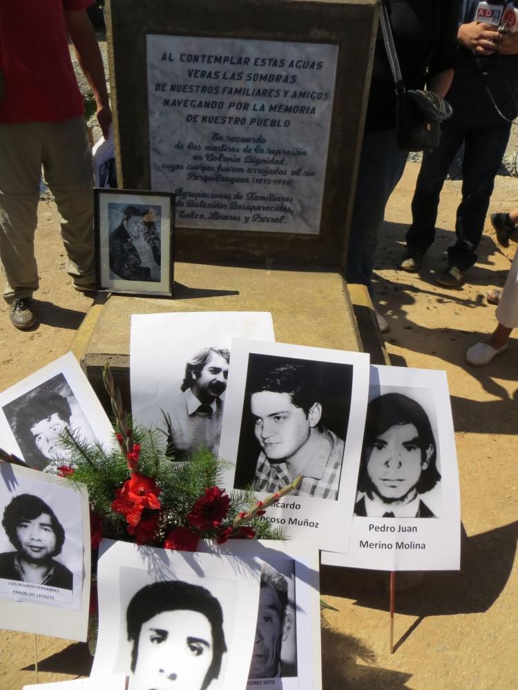 Vor dem Gedenkstein liegen Fotos von Verschwundenen