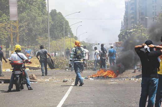 Demonstranten vor brennenden Barrikaden im Bundesstaat Bolívar