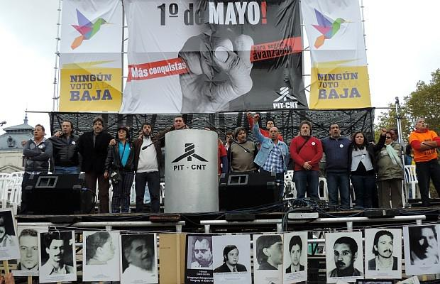 """Gewerkschaftsführer riefen zur Schaffung eines  """"neuen produktiven Modells"""" auf. Vor dem Podium: Bilder von während der Diktatur """"Verschwundenen"""", deren Schicksal noch aufgeklärt werden muss"""