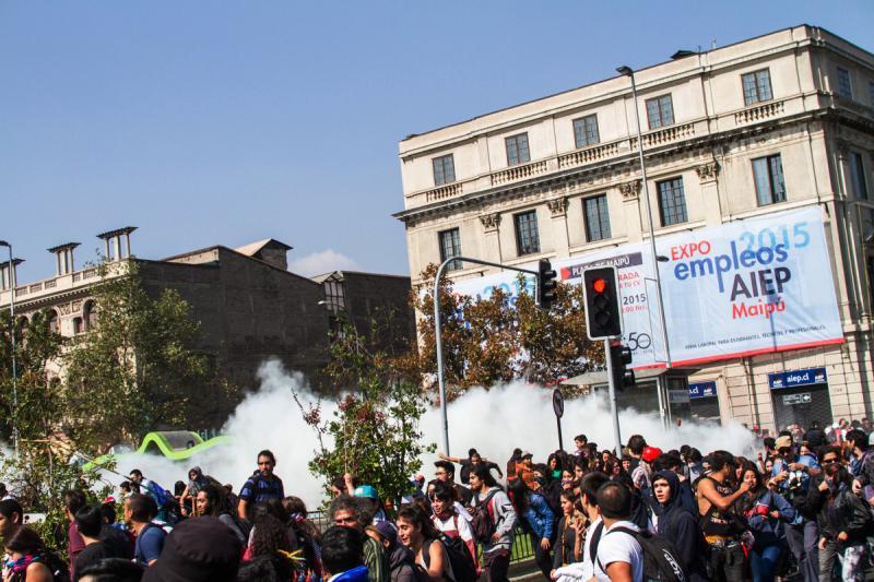 Eine Tränengaswolke steigt hinter Demonstranten auf