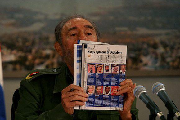 """Fidel Castro mit einer Ausgabe des US-Wirtschaftsmagazins Forbes vom Mai 2005, wo er unter dem Titel """"Könige, Königinnen und Diktatoren"""" als eine der reichsten Personen der Welt gelistet wird. Forbes hatte kurzerhand sämtlichen kubanischen Staatsbesitz zu Castros Privatvermögen erklärt"""