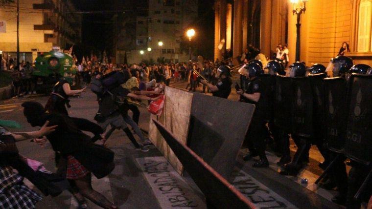 Demonstrantinnen versuchen, die Absperrungen beiseite zu räumen