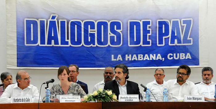 Rita Sandberg (Norwegen) und Rodolfo Benitez (Kuba) verlasen das Dokument. Neben ihnen die Leiter der Friedensdelegationen der Regierung Kolumbiens, Humberto de la Calle (links) und der Farc, Iván Márquez