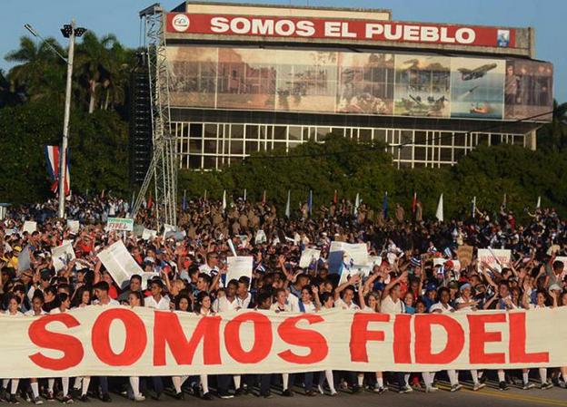 """""""Wir sind Fidel"""" – Leittransparent zum 60. Jahrestag der Revolution in Kuba. Am Gebäude im Hintergrund: """"Wir sind das Volk""""."""