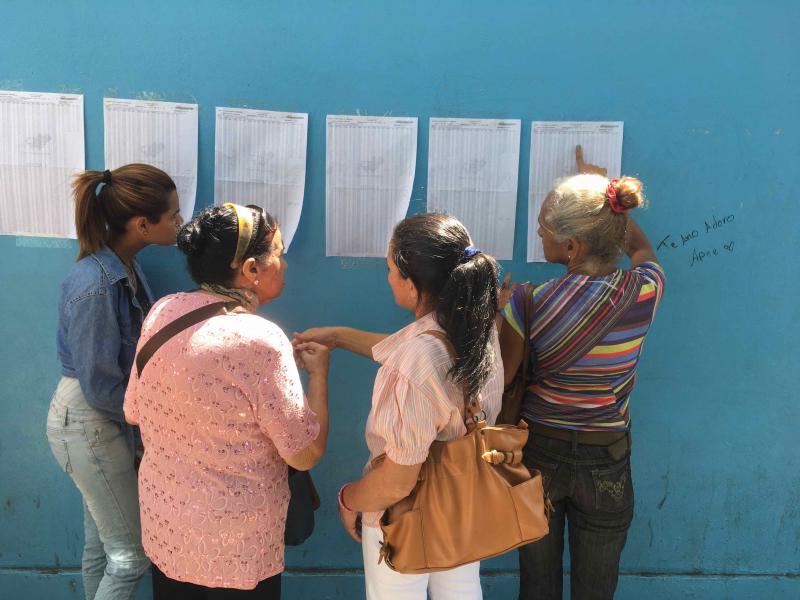 Venezolanerinnen überprüfen vor einem Wahlzentrum ihre Ausweisnummer, um das für sie vorgesehene Wahllokal zu finden