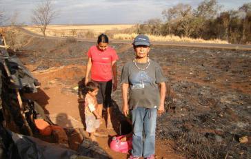 Damiana Cavanha, Anführerin der Gemeinde Apy Ka'y, steht neben den Resten ihres Lagers, nachdem es bei einem Feuer zerstört wurde