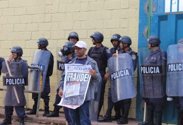 Demonstrant hält in Honduras vor Polizisten eine Zeitung
