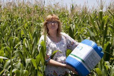 Aktivistin mit einem Glyphosat-Behälter in einem Maisfeld in Argentinien