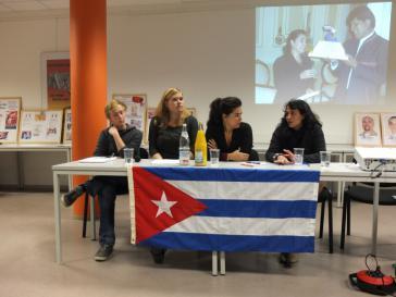 Bei der Veranstaltung in Berlin. Links von Adriana Pérez zwei Teilnehmer der SDAJ-Cuba-Brigade im August 2013, rechts die Übersetzerin. Auf dem Hintergrundbild: Adriana Pérez mit Boliviens Präsident Evo Morales