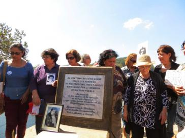"""Der Gedenkstein trägt die Inschrift: """"Wenn Du in diesen Fluß schaust, siehst Du die Schatten unserer Freunde und Angehörigen durch die Erinnerung unseres Volkes segeln – In Gedenken an die Märtyrer der Repression der Colonia Dignidad deren Körper in den Perquilauquén geworfen wurden (1973-1990) Organisation der Angehörigen der Verschwundenen Talca – Linares – Parral"""""""