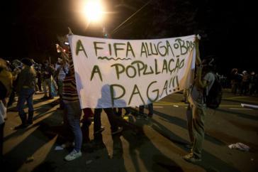 """Protestplakat: """"Die FIFA mietet sich ein und die Bevölkerung bezahlt"""""""
