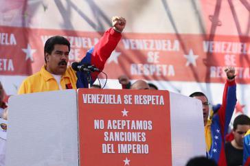 """Präsident Maduro kritisiert die Sanktionen scharf.  Auf dem Podium geschrieben steht: """"Venezuela wird respektiert - wir akzeptieren keine Sanktionen durch das Imperium"""""""