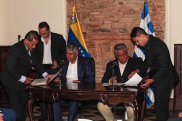 Tsipras und González (sitzend) bei der Unterzeichnung der Absichtserklärung