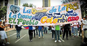 """Friedensdemonstranten mit Transparent: """"Die kolumbianische Bevölkerung hat den Schlüssel zum Frieden"""""""