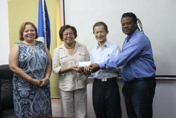Botschafter Benjamin Ho (2. von rechts) überreicht Regierungsvertretern von Belize einen Scheck über 100.000 US-Dollar