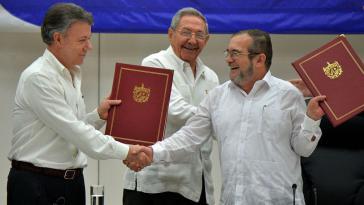 Präsident Santos und der Farc-Oberkommandierende Timoleón Jiménez nach Unterzeichung des Abkommens. Hinter ihnen Kubas Präsident Raúl Castro