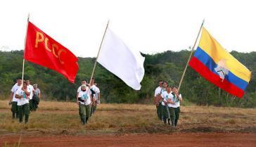 Drei Fahnen bei der 10. Guerillakonferenz: die der verbotenen kommunistischen Partei, die Friedens- und die Farc-Fahne