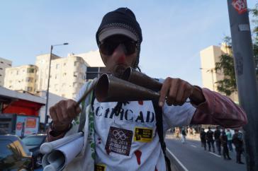 Ein Demonstrant weist auf soziale Verdrängung durch die Olympischen Spiele hin.