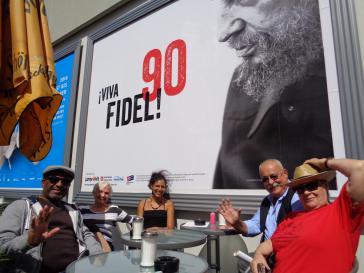 Aktivisten vor dem Geburtstags-Plakat für Fidel Castro in Berlin