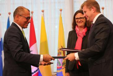 Ecuadors Vizepräsident Jorge Glas und die Vertreter der EU tauschen das unterzeichnete Abkommen aus