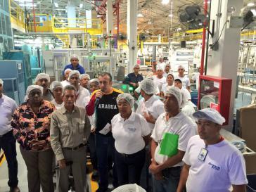 Araguas Gouverneur El Assaimi und Arbeitsminister Vera mit Arbeiterinnen und Arbeitern beim Rundgang im Werk