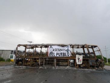 """Straßensperre mit ausgebranntem Bus. Auf dem Transparent: """"Mörder des Volkes"""" mit den Konterfeis von Präsident Peña Nieto und Innenminister Osorio Chong"""
