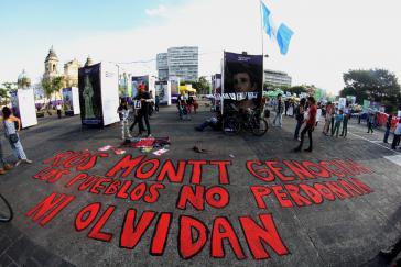 """Versammlung von Familienangehörigen und Betroffenen des Völkermordes am Todestag des Diktators. Auf den Boden geschrieben steht: """"Ríos Montt Völkermörder. Die Völker vergessen nicht und vergeben nicht."""""""