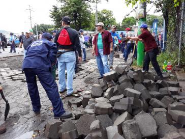 Nach der Räumung von Straßensperren reparieren Gemeindearbeiter und Bürger gemeinsam eine Straße in Masaya, Nicaragua