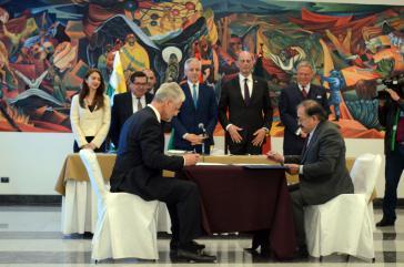 Bolviens Vizepräsident García Linera und Thüringens Wirtschafts- und Wissenschaftsminister Tiefensee (stehend hinten) bei der Unterzeichnung des Vertrages