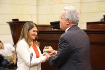 Die Farc-Senatorin Griselda Lobo alias Sandra Ramírez übergibt Ex-Präsident Álvaro Uribe eine Pflanze als Symbol des Friedens