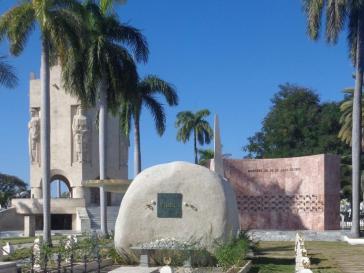 """In Anlehnung an José Martís Ausspruch, dass """"aller Ruhm der Welt in ein Maiskorn passt"""", wurde der Naturfelsen aus der Sierra Maestra, der als Fidel Castros Grabstein dient, nach dieser Form bearbeitet und schlicht gehalten. Links im Hintergrund: das Mausoleum Martís"""