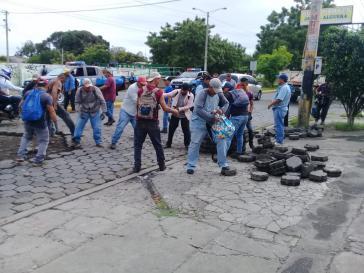 Nach der Beseitigung einer mit Pflastersteinen errichteten Straßenblockade reparieren Anwohner eine Straße in Managua, Nicaragua