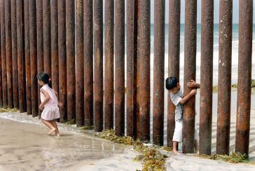 Kinder schlüpfen durch eine Grenzbefestigung zwischen den USA und Mexiko