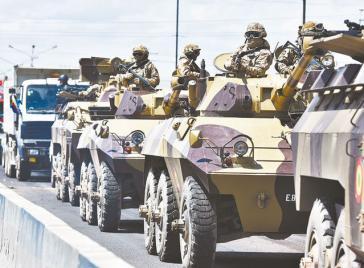 Soldaten fahren auf Panzern mit Maschinengewehren durch Senkata in der Stadt El Alto, Bolivien