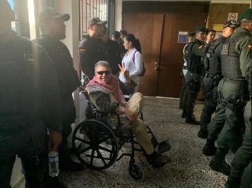 Jesús Santrich im Rollstuhl auf dem Weg zum VErhandlungssaal bewacht von Polizeikräften