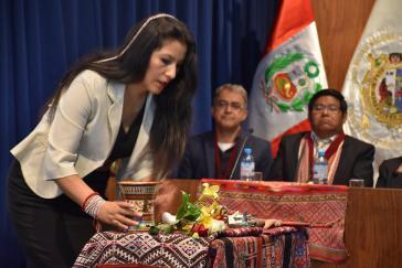 Zu Beginn der Verteidigung ihrer Doktorarbeit widmete Quispe der Erde eine Gabe mit Kokablättern und Chicha-Getränk
