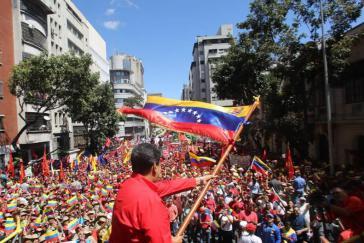 Zehntausende demonstrierten am Samstag in Caracas gegen Interventionismus und Krieg. Im Vordergrund Präsident Maduro mit der Landesflagge