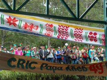 """Mitglieder der Selbstverteidigungseinheiten """"Guardia Indigena"""" erheben während der Hymne der Bewegung ihren Baston de Mando, das Autoritätsymbol der Amtsträger."""