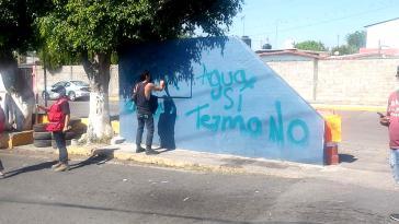 Ein Demonstrant betont die Ablehnung des Kraftwerkprojektes durch ein Graffito