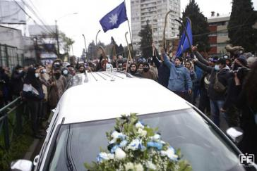 Ein Leichenwagen, hinter ihm protestierende Mapuche.