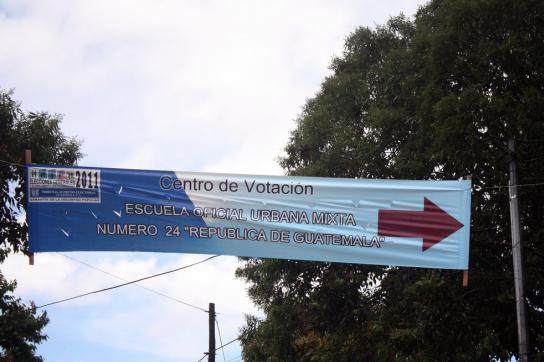 Transparent vor einem Wahllokal mit Pfeil nach rechts