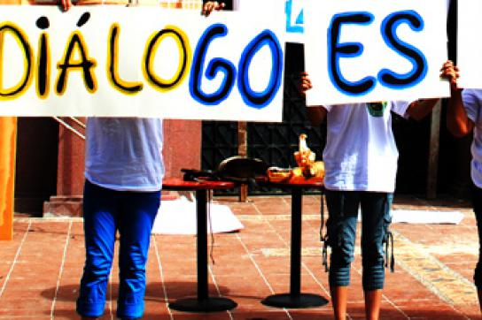"""Menschen mit Schildern auf denen steht: """"Der Dialog ist der Weg"""""""