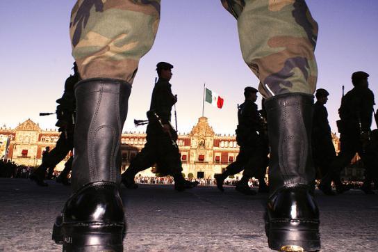 Soldaten auf einem Platz. Im Hintergrund die mexikanische Fahne
