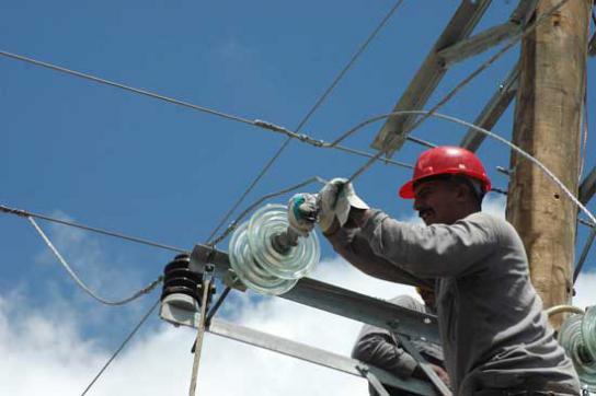 Arbeiter repariert Stromleitung in Kuba