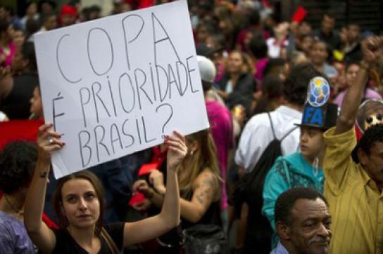 """Demonstrantin mit Plakat """"WM - Priorität für Brasilien?"""""""