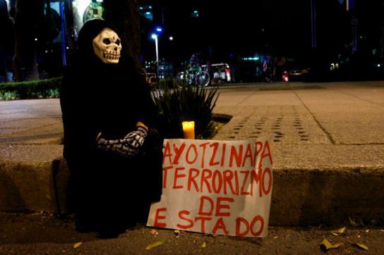 """Demonstrant mit Totenkopfmaske und Transparent: """"Ayotzinapa - Staatsterrorismus"""""""